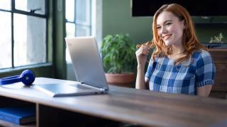 Mujer mirando portátil y sonriendo